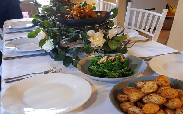 family dinner party celebration with food to share in the middle table plates and cutley